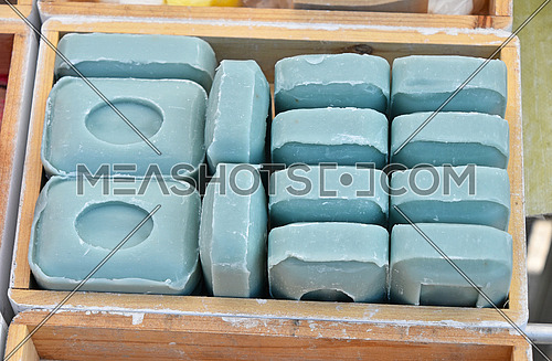 Close up blue traditional beauty toilet hard soap bars in wooden box on retail display, high angle view