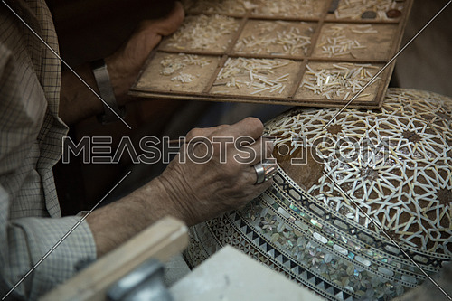 Decorating the back of an Oud with Islamic designs made of Shell