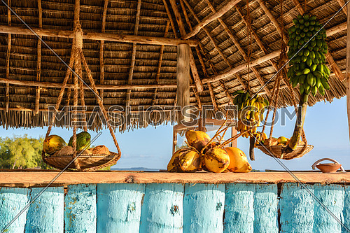 In the picture beach bar in Nungwi ( Zanzibar ) at sunset , with exposed coconut , banana and tropical fruit .This bar is made with cane bamboo,wooden and straw rope.