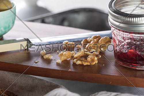 Walnuts beside a knife and jar of jam on a wooden board
