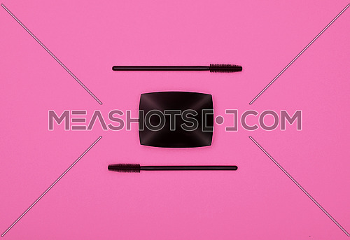 Close up set of face makeup black mascara brushes and eye shadows over pink background, elevated top view, directly above