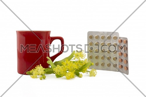 Red cup near freshly picked yellow linden flowers and pills in a blister over a white background, alternative treatment of linden blossom tea