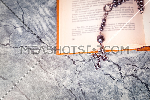 Black rosary and cross on the Bible on a gray surface. Religion at school.