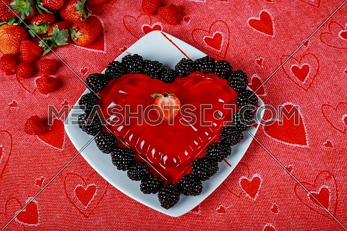 Sweet dessert in jelly in the form of a heart on a glass dish.
