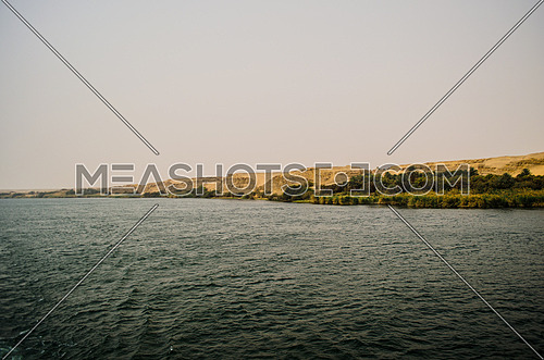 A landscape of the Nile river water and sand mountains by the shore and plants