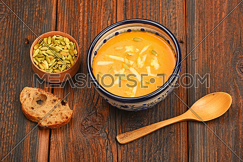 Ceramic bowl of pumpkin cream soup, spoon, slice of bread and seeds on dark wooden table background, high angle view