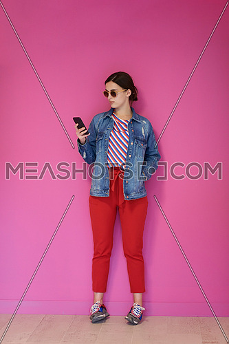 Portrait of young girl using smartphone while standing in front of pink background. Female model wearing sunglasses representing modern fashion and technology concept