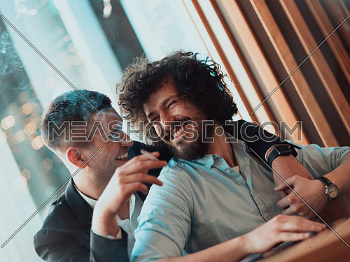 two lgbt guys sit romantically embracing in a modern cafe while smoking cigars