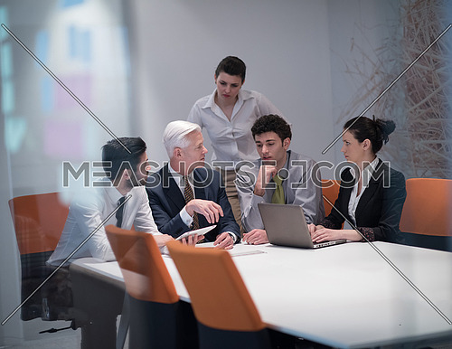 Young business people group on meeting at modern startup office with  senior manager.  Team leader looking presentation and  results  on tablet and laptop computer.