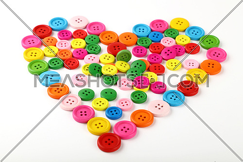 Heart shaped of colorful multicolor round painted wooden handmade sewing buttons isolated on white, close up, low angle view
