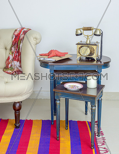 Interior shot of old golden telephone set, white candle, red starfish and colorful ornate plate over three nested tables with blue legs over off white wall, colorful Capet, and cream armchair
