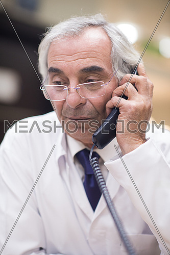 Senior middle eastern doctor talking on the phone in a large modern clinic