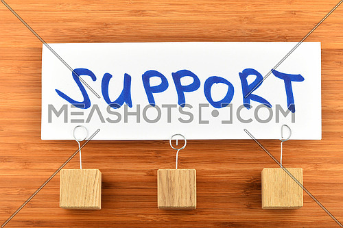 Support, one big white paper note with blue hand written text and three wooden holders on bamboo background for presentation