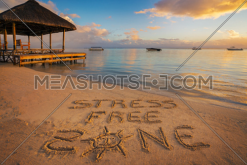 "Forground written in the sand ""stress free zone"" at sunset in Mauritius Island with Jetty silhouette and Fishermen's boats in the background."