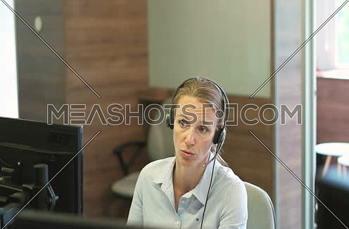blonde talking on headset in a call center