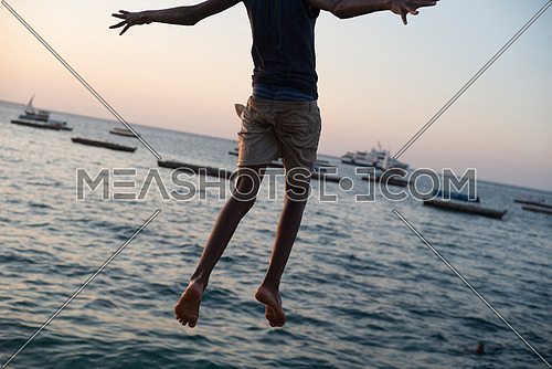 A man jumping high towards the ocean