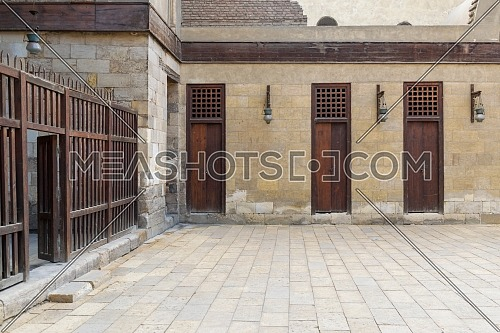Three adjacent doors in a stone bricks wall and wooden fence at the main courtyard of public historic mosque of Sultan Al Nassir Qalawun, Cairo, Egypt