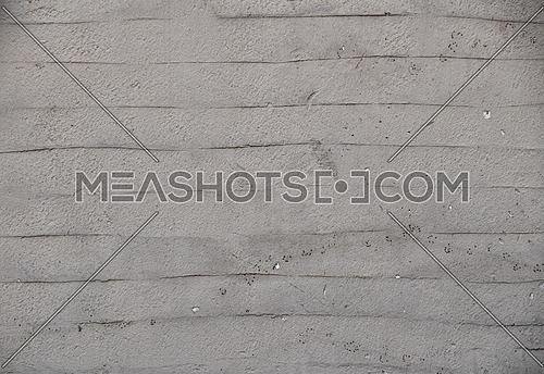 Rough uneven gray beige wall surface of decorative wavy embossed painted lime plaster background texture, close up