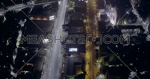 Aerial top shot flying over 6 of October Bridge showing Abd Elmonan Reyad Bus Station At Tahrir Area then reveals Cairo sky horizon in cairo at night