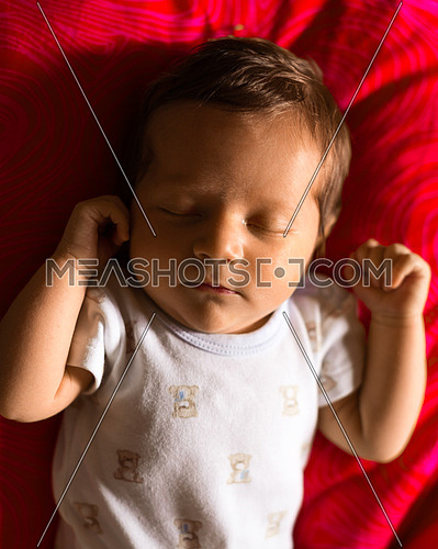 Newborn boy sleeping peacefully on a red background