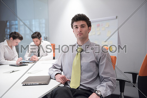 portrait of young business man with curly hair and  at modern bright office  interior with big windows in background