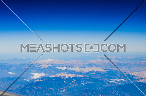 Clear blue sky with clouds and top of the mountains appears underneath and among the clouds