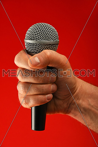 Man hand holding voice microphone in fist over red background