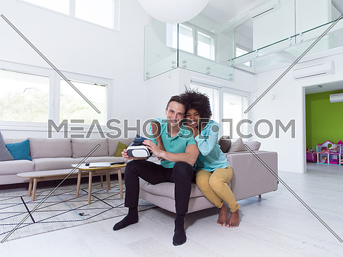 Multiethnic Couple using virtual reality headset in living room at home  people playing game with new trends technology