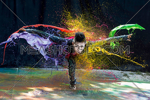 A man doing an acrobatic move with a splash of colors on a dark background