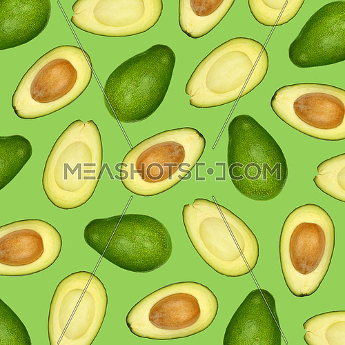 Pattern of fresh halved cut and whole avocados over green background