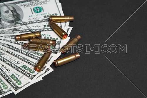 Closeup for used bullet shells and dollars on black table.