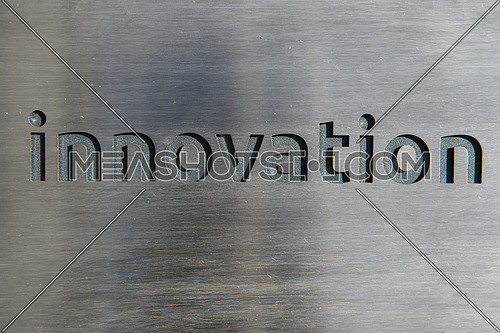 Engraving a CNC machine on a piece of metal. Engraving innovation text. High quality photo