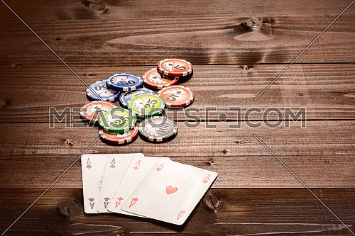 Four aces and chips, vintage poker game playing cards on a wood table