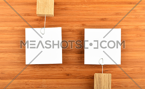 Opposite Opinions - Two white paper notes with wooden holders in different directions on bamboo wooden background for presentation