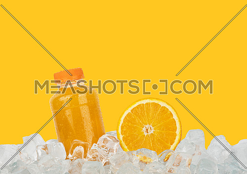 Close up one plastic PET bottle full of fresh orange juice and cut half orange slice on ice cubes isolated on yellow background, low angle side view
