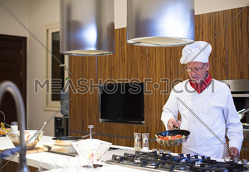 Senior middle east chef's fried meal in the kitchen with satisfaction