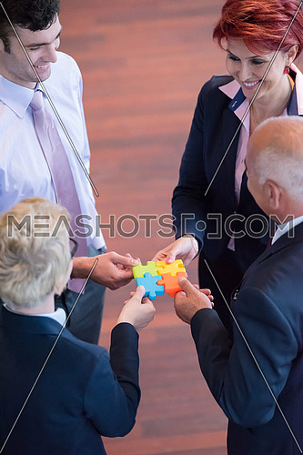 diverse business people group assembling jigsaw puzzle and represent team support and help concept, top view perspective at modern bright office interior