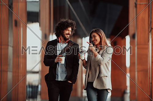 two young people on a break from work walk in front of the modern firm in which they work