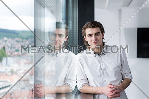 portrait of young businessman at startup office by the window