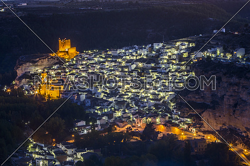 Alcala del Jucar, Spain - October 29, 2016: Night view of the city, on top of limestone mountain is situated Castle of the 12TH century Almohad origin, take in Alcala of the Jucar, Albacete province, Spain