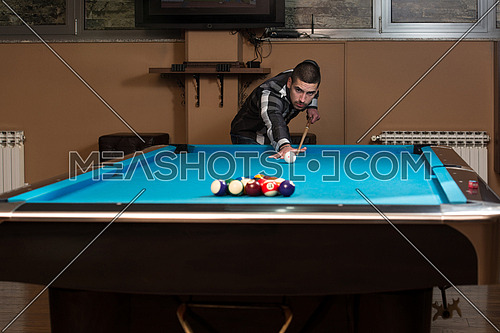 Young Man Lining To Hit Ball On Pool Table