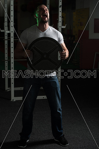 Portrait Of A Man In Jeans Holding Weights In Hand In A Dark Gym