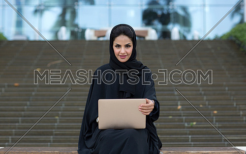 Arab lady setting and working with her laptop