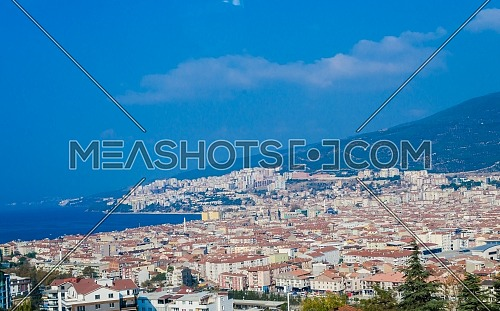 Landscape of a Turkish city by the ocean showing houses and small buildings and mosques