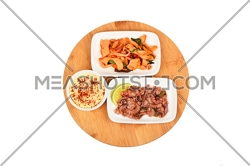 Two portions of seafood marinated salad with octopus cuttlefish and squid calamari with mayo sauce on round wooden bamboo board, top view