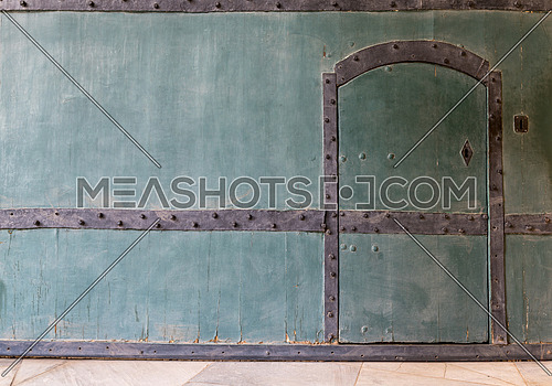 Closed wooden blue door in a wooden blue wall and marble floor