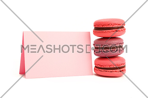 Stack of colorful traditional French macaroon pastry cookies (macarons, macaroni) with pink paper sign isolated on white background, close up, low angle view