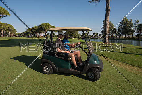 golf players driving cart at course on beautiful morning sunrise. friends together have fun and relax on vacation.