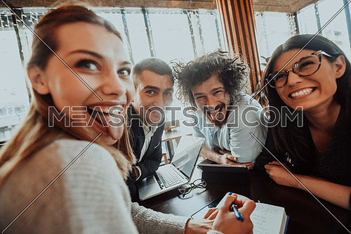 an entertaining portrait of young entrepreneurs sitting in a modern office and using modern devices