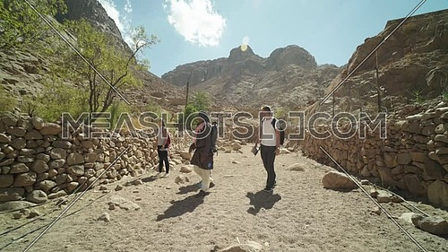 Reveal shot for group of tourists walking on big rocks between two fences of rocks with bedouin guide showing almond trees while explore Sinai Mountain for wadi Freij at day.